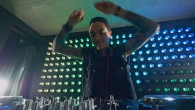 A DJ in close view turns knobs with both hands. A DJ claps his hands and turns two mixer knobs at once stock video footage