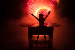 Dj club concept. Woman DJ mixing, and Scratching in a Night Club. Girl silhouette on dj's deck, strobe lights and fog on royalty free stock image