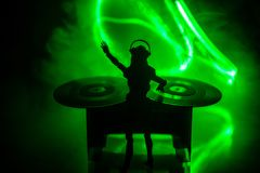 Dj club concept. Woman DJ mixing, and Scratching in a Night Club. Girl silhouette on dj\'s deck, strobe lights and fog on stock photo
