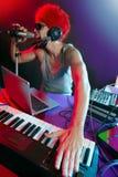 DJ com luz colorida e equipamento de mistura da música Fotografia de Stock