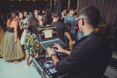 DJ com os fones de ouvido no partido do clube noturno sob a multidão colorida da luz e dos povos no fundo DJ no partido aberto de imagens de stock royalty free