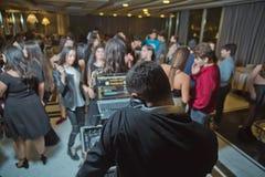 DJ com os fones de ouvido no partido do clube noturno sob a multidão colorida da luz e dos povos no fundo DJ no partido aberto de fotografia de stock royalty free