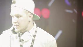 DJ con los auriculares que hacen girar en la placa giratoria en partido en club nocturno aclamación Proyector almacen de video