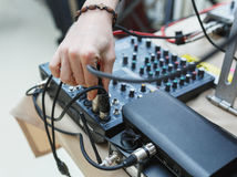 DJ connects the sound equipment for the event or party. Stock Photos