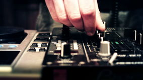 DJ at a console booth spinning and touching mixer faders and knobs stock footage