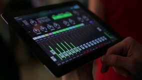DJ controleert de muziek met de tablet en de equaliser, stock videobeelden