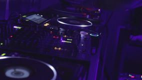 Dj controls the sound in nightclub hands do active moves on mixer and turntable. Stock footage stock video footage