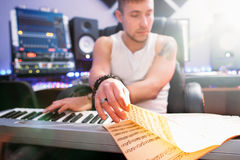 DJ create piano music in recording studio. DJ create club music in sound recording studio. Musician looks into notes and playing the electronic piano.  Composer Stock Photo