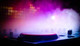 DJ, das in einem Nachtclub, Hände von DJ spinnt, mischt und verkratzt, zwicken verschiedene Bahnkontrollen auf Plattform, Runduml Stockbilder