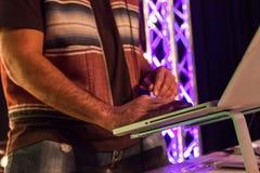 DJ, das raue Baumwollärmellose Jacke trägt, verzeichnet zwar seine Musik in einer Liste lizenzfreie stockfotografie