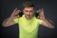 DJ, das seine Kopfhörer hält Lizenzfreie Stockbilder