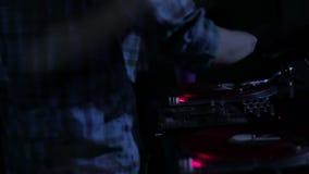 DJ, das Vinylaufzeichnungen verkratzt und auf den Plattformen an einer Disco im Nachtklubschleifenvideo mischt stock video
