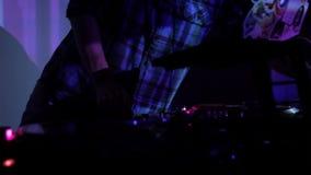 DJ, das Vinylaufzeichnungen verkratzt und auf den Plattformen an einer Disco im Nachtklubschleifenvideo mischt stock video footage
