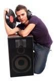 DJ dat in hoofdtelefoons een plaat houdt Stock Afbeelding