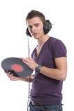 DJ dat in hoofdtelefoons een plaat houdt Stock Fotografie