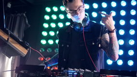 DJ die glazen dragen bij een mixertribune stock footage