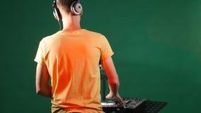 DJ die muziek mengen die zich bij zijn dek, dans in zijn oortelefoon, van de rug bevinden stock foto