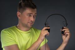 DJ die zijn hoofdtelefoons houden Royalty-vrije Stock Afbeelding