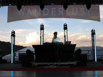 DJ Drez spins on stage during concert with mountain landscape Stock Photography