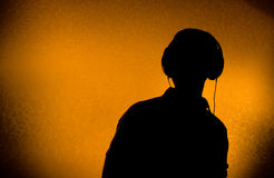 DJ with earphones. Silhouette of male DJ with earphones (back light Royalty Free Stock Images
