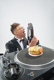 Dj eating donut on working place turntable Stock Photos