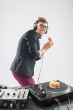 Dj eating donut on working place turntable Stock Images