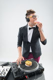 Dj eating donut on working place turntable Stock Photography