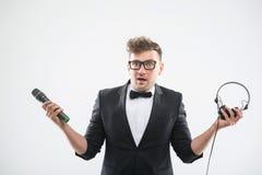DJ en el smoking que sostiene el micrófono y los auriculares Imagenes de archivo
