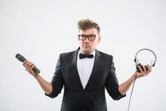 DJ en el smoking que sostiene el micrófono y los auriculares Fotografía de archivo