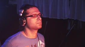 DJ en los auriculares que hacen girar en la placa giratoria en partido en club nocturno Proyectores rojos hospitalidad holiday almacen de metraje de vídeo