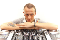 DJ with equipment. A happy DJ and his turntables, mixers, cd/mp3 players, funcky white headphones Stock Photo