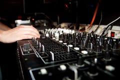 DJ está mezclando música en la consola de la música Imagen de archivo