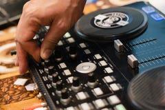 DJ est? tocando reguladores foto de archivo