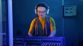DJ femenino con los auriculares en un cuarto técnico conduce un disco en una consola de mezcla teniendo en cuenta un disco almacen de metraje de vídeo