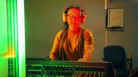 DJ femenino con los auriculares en un cuarto técnico conduce un disco en una consola de mezcla teniendo en cuenta un disco metrajes