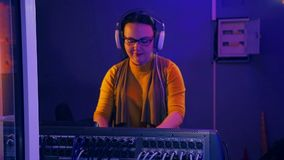 DJ femenino con los auriculares en un cuarto técnico conduce un disco en una consola de mezcla teniendo en cuenta un disco almacen de video
