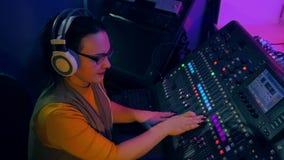 DJ femenino en los auriculares que mezclan las pistas para el disco en una consola de mezcla metrajes