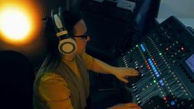 DJ femenino en los auriculares que mezclan las pistas para el disco en una consola de mezcla almacen de metraje de vídeo