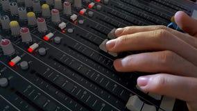 DJ Fingers control the sound on audio mixer stock video