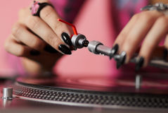 DJ fitting needle to turntable tonearm. Hands of female disc jockey adjusting professional sound euqipment Royalty Free Stock Photo