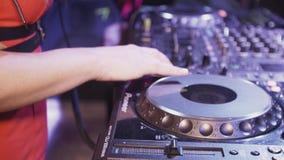 Dj-flicka i röd klänningsnurr på skivtallriken i nattklubb utrustning mix musik stock video