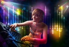 Dj-flicka som spelar sånger i ett disko med ljus show royaltyfri bild