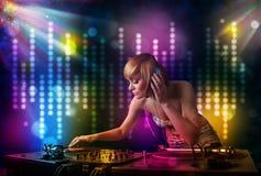 Dj-flicka som spelar sånger i ett disko med ljus show Royaltyfri Fotografi