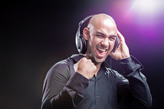 Dj forming a fist while holding his headphones Stock Image