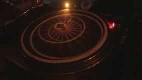 DJ fresco atrás das plataformas giratórias que executam em uma barra filme