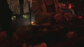 DJ fresco atrás das plataformas giratórias que executam em uma barra vídeos de arquivo