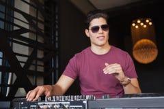 DJ fresco en las gafas de sol que trabajan en un escritorio de mezcla sano Imagen de archivo