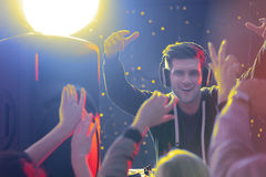 Dj in front of crowd. Happy dj in front of crowd, playing at nightclub Stock Image