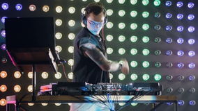 A DJ gets back to mixing sets. A DJ at a mixer stand puts on headphones to continue his work stock video footage