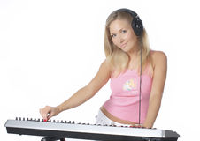 DJ girl. Young beautiful woman with headphones playing piano. Playing midi-keyboard. DJ-girl playing electronic music. Isolated on white Royalty Free Stock Image